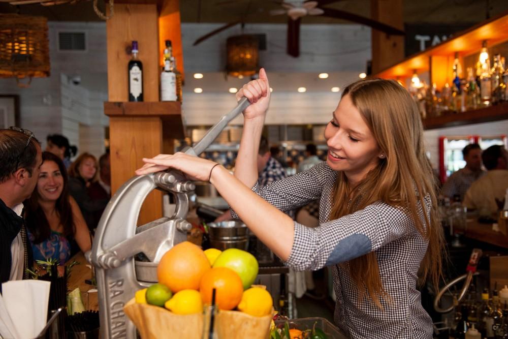 bartaco staff squeezing fruit in juice presser
